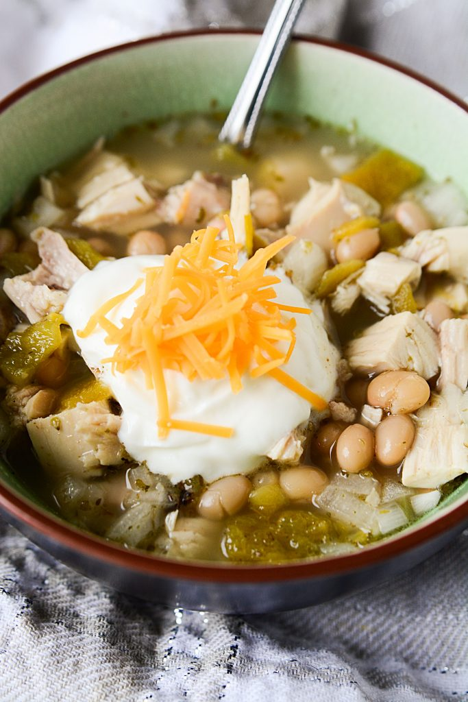 Super easy slow cooker Crock Pot White Chicken Chili Recipe. Chili is a great comfort food, especially in the winter after spending the day outdoors. You and your family will all go for seconds for this creamy deliciousness!