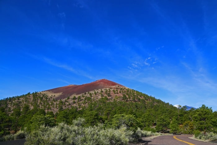 wide view of Sunset Crater Volcano in Arizona with a bright blue background.