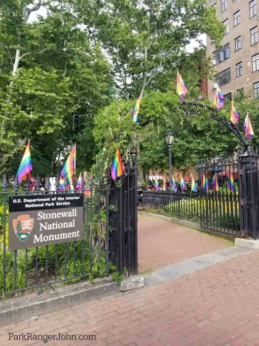 Entrance to Christopher Park in New York with a sign for Stonewall National Monument and Rainbow Flags