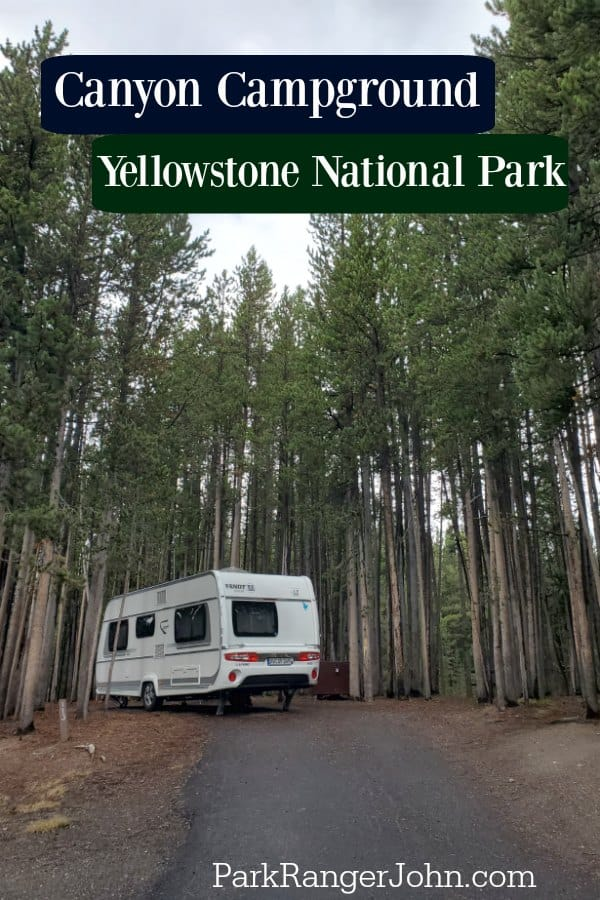 White rv parked in a campsite surrounded by trees in the Canyon Campground, Yellowstone National Park.