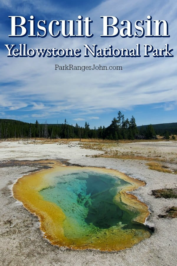 Orange and green thermal pool along Biscuit Basin boardwalk in Yellowstone National Park, blue skies and trees in the background.