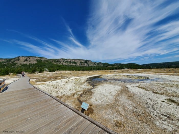 Biscuit basin wooden boardwalk along the left side next to Jewel Geyser with white clouds above