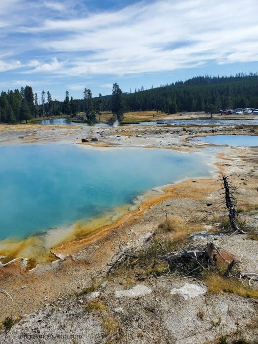 Bight turquoise with orange rim thermal pool with the firehole river in the background and blue skies.